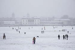 © Licensed to London News Pictures. 24/01/2021. London, UK. Members of the public exercise in a snowy Greenwich park in South East London. Snow is expected for large parts of the UK and a yellow weather warning is in place in parts of England. Photo credit: George Cracknell Wright/LNP