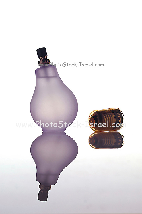 A perfume bottle shaped as a light bulb on white background with a reflection