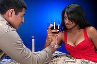 Young hispanic couple celebrating and toasting at night club or restaurant setting.