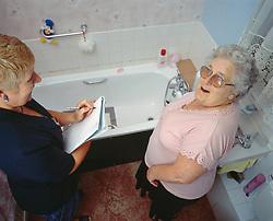 Housing estate manager with elderly woman tenant checking bathroom, London Borough of Haringey UK