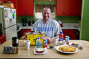 Todd Kincer, a coal miner, with his typical day's worth of food and his workday lunch box at his home in Mayking, Kentucky. (From the book What I Eat: Around the World in 80 Diets.) The caloric value of his day's worth of food in the month of April was 3,200 kcals. He is 34 years of age; 5 feet, 11 inches tall; and 185 pounds. After showering and scrubbing off the day's coal dust, Todd gets ready to dig in to one of his favorite meals: Hamburger Helper with double noodles. A college graduate drawn to the coal mine by the relatively high pay, Todd spends a 10-hour shift mining underground, driving a low-slung electric shuttle car that carries coal from the face of the coal seam, where it's being chewed up by a deafening, dusty mining machine, to a conveyer belt. The mine, located deep inside a mountain in the Appalachians near the town of Whitesburg, Kentucky, is pitch-black, except for headlights and headlamps. During winter months, Todd never sees daylight during the workweek. MODEL RELEASED.