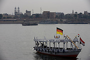 A privately-owned motorboat ferry flying the German flag and dependent on all tourist trade crosses the River Nile at Luxor, Nile Valley, Egypt.