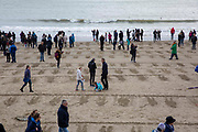 "The commminuty gather to remember fallen soldiers on the beach in Folkestone as part of Danny Boyle's 'Pages of the Sea""  Armistice Day event commemorating 100 years since the end of the First World War on remembrance day the 11th of November 2018. Sunny Sands beach, Folkestone, Kent, United Kingdom."