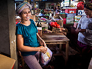 07 AUGUST 2017 - BEBANDEM, BALI, INDONESIA:  A woman takes a break while shopping in the market in Bebandem, in far eastern Bali. The market is known for baskets, which are woven in the area. Bali's local markets are open on an every three day rotating schedule because venders travel from town to town. Before modern refrigeration and convenience stores became common place on Bali, markets were thriving community gatherings. Fewer people shop at markets now as more and more consumers go to convenience stores and more families have refrigerators.    PHOTO BY JACK KURTZ