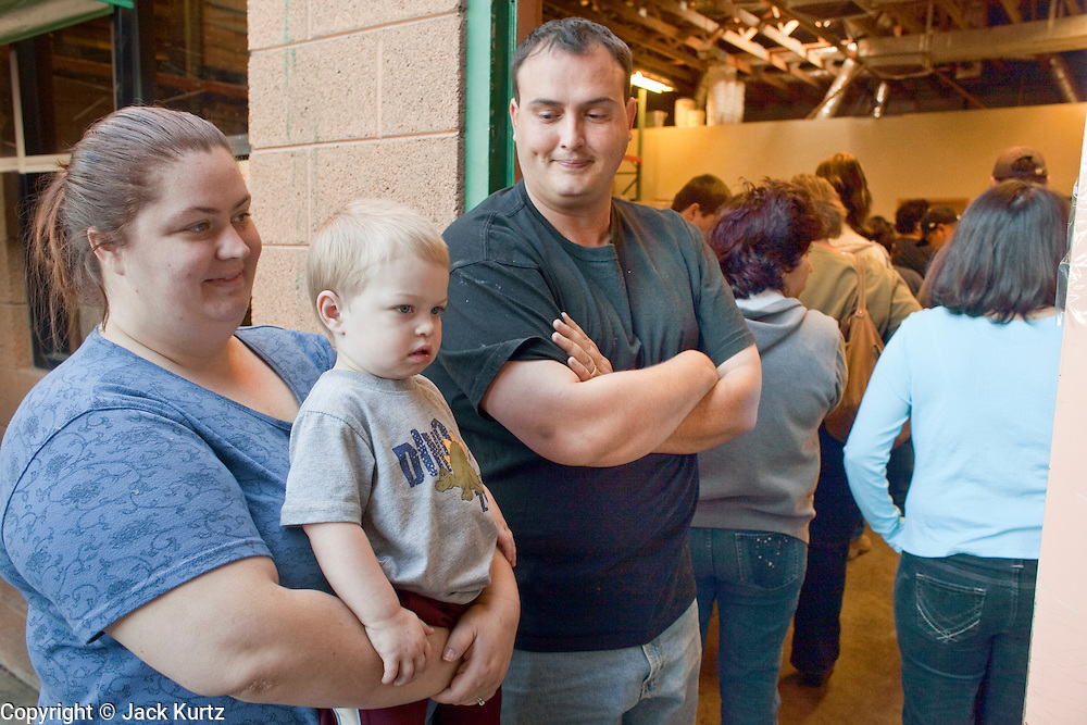 Apr. 3, 2009 -- MESA, AZ: KATRINA HALL, left, her husband, TIM HALL and their son, ZANE HALL, from Tempe, AZ, wait in line at the United Food Bank in Mesa, AZ. Hall said he drives a tourist bus but as the tourism and leisure industry has suffered in the recession his work in disappearing and in March he only work five days. A spokesperson for the United Food Bank in Mesa, AZ, said demand has increased by more than 100 percent in the last year. She said that at this time in 2008, about 175 people a week (the food bank is open one day a week) bought 200 boxes a food but now they were seeing about 350 people per week and they were buying 400-450 boxes of food per week. Each box of food cost $16 and contains enough food for five meals for two people, including meat, fruit and vegetables and starches. In addition to the food boxes, the food bank gives away perishables, like fresh baked goods and produce, that are donated by Phoenix area grocery stores and food producers. She said the number of donations to the food bank have increased as the economy has worsened but each donation is smaller and the gap between donations and what the food bank needs is widening.    Photo by Jack Kurtz / ZUMA Press