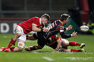 Carl Meyer of the Newport Gwent Dragons offloads the ball in a tackle.<br /> Guinness Pro12 rugby match, Munster v Newport Gwent Dragons at Thomond Park in Limerick , Ireland on Saturday 5th March 2016.<br /> pic by  John Halas, Andrew Orchard sports photography.