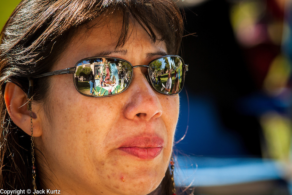 21 JUNE 2012 - PHOENIX, AZ:  An altar honoring the Virgin of Guadalupe in reflected in the sunglasses of ROSE DOMINGUEZ in front of the Arizona State Capitol Thursday. About 40 people, members of the immigrant rights' group Promise AZ (PAZ), gathered at the Capitol in Phoenix to wait for the US Supreme Court decision on SB 1070, Arizona's controversial anti-immigrant law, in the case US v. Arizona. The court's ruling is expected sometime later this month. Members of PAZ said they would continue their vigil until the ruling was issued.        PHOTO BY JACK KURTZ