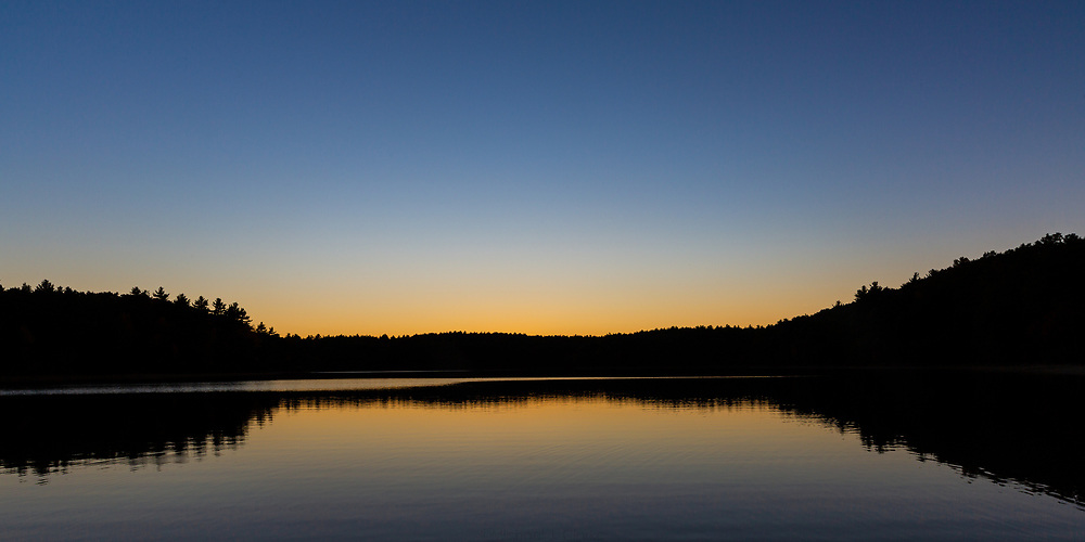 A colorful autumn sunset at Walden Pond in Concord, MA.