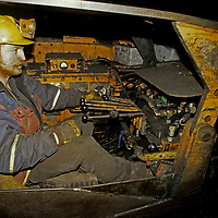 Working deep underground on a polar island, a Norwegian coal miner operates heavy machinery dragging coal out of seams where it has been blasted loose from the bedrock.