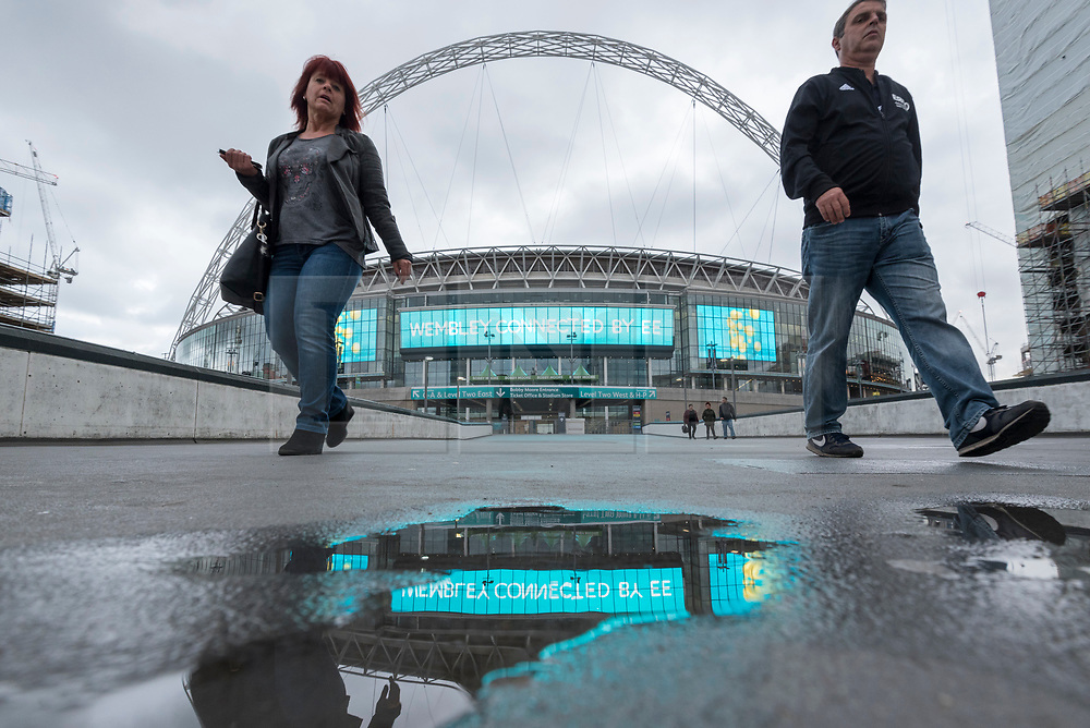 © Licensed to London News Pictures. 17/10/2018. LONDON, UK.  Tourists walk by Wembley Stadium.  Shahid Khan, owner of Fulham FC and the Jacksonville Jaguars NFL team, has withdrawn his £600m offer to buy the stadium, amidst reports that he did not feel that he would receive sufficient support from The Football Association (FA).  The FA was due to vote on the potential sale on October 24.  Photo credit: Stephen Chung/LNP