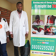 INDIVIDUAL(S) PHOTOGRAPHED: Adigun Abiola (left) and Dr. Ogundimu Opeyemi (right). LOCATION: Lagos State University Teaching Hospital Dot Clinic, Lagos, Nigeria. CAPTION: A doctor from the tuberculosis unit and the head of the pharmacy pose in front of an information poster, which details the symptoms of tuberculosis.