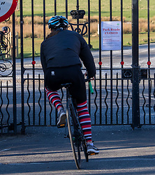 © Licensed to London News Pictures. 23/03/2020. London, UK. A cyclist looks at a sign saying Park Roads Closed which has been posted on the gates of Roehampton Gate, Richmond Park this morning. Royal Parks have temporarily banned all cars from entering Richmond Park, Bushy Park and Greenwich Park after a huge surge in traffic on Saturday and Sunday with large numbers of people ignoring the social distancing guidelines. Cyclists and walkers can continue to enter the parks as the coronavirus crisis continues. Photo credit: Alex Lentati/LNP