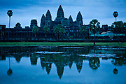 Angkor Wat, the Hindu temple and its reflection in the surrounding water before sunrise, Cambodia.