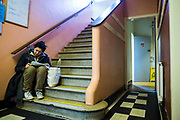 A young homeless lady sitting on the stairs reading the paper. Slough Homeless our concern (SHOC) A local homeless charity helping the homeless and vulnerable in Slough. Berkshire, UK.