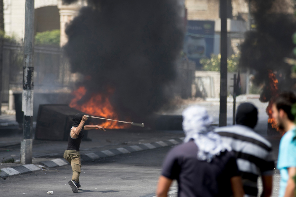 Bethlehem, Palestine. 15 May 2018. A protester uses a slingshot to throw a rock towards Israeli soldiers on the 70th anniversary of the Nakba (Catastrophe) when over 700,000 Palestinians were forcibly moved from their homes during the creation of Israel. © Craig Redmond
