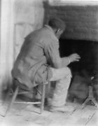 African American, possibly a former slave, sitting warming himslef by the fire in his room. Photograph c1800.