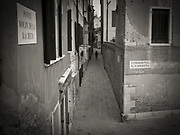 Toned photograph of narrow Venice, Italy street with a woman walking