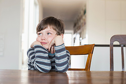 Boy leaning on wooden table, looking away