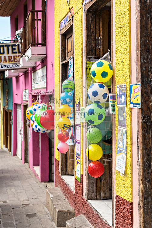 A bright yellow building colorful balls on a shop in Angangueo, Michoacan, Mexico. Angangueo is a tiny, remote mountain town and the entry point to the Sierra Chincua Monarch Butterfly Sanctuary.