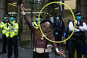 An activist from HS2 Rebellion, an umbrella campaign group comprising longstanding campaigners against the HS2 high-speed rail link as well as Extinction Rebellion activists, uses a hula hoop during a protest outside the Department for Transport on 4 September 2020 in London, United Kingdom. Activists glued themselves to the doors and pavement outside the building and sprayed fake blood around the entrance during a protest which coincided with an announcement by HS2 Ltd that construction of the controversial £106bn high-speed rail link will now commence.