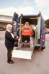 Woman with disability; who is wheelchair user; being lifted into adapted van,