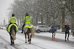 © Licensed to London News Pictures. 24/01/2021. London, UK. Mounted Police officers patrol Greenwich Park during a snow shower. Snow is expected for large parts of the UK and a yellow weather warning is in place in parts of England. Photo credit: George Cracknell Wright/LNP