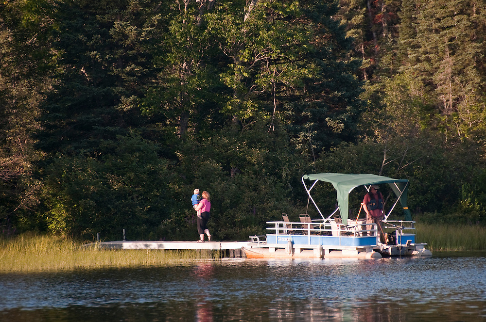 A short pontoon boat ride ferries visitors to the Republic Island Cottage on the Michigamme River near Republic Michigan.