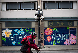 A pedestrian and cyclist pass a closed business with a mural that says 'Stay Apart' on the boarded up windows, in downtown Vancouver, BC, Canada on Sunday, April 19, 2020. TPhoto by Darryl Dyck/CP/ABACAPRESS.COM