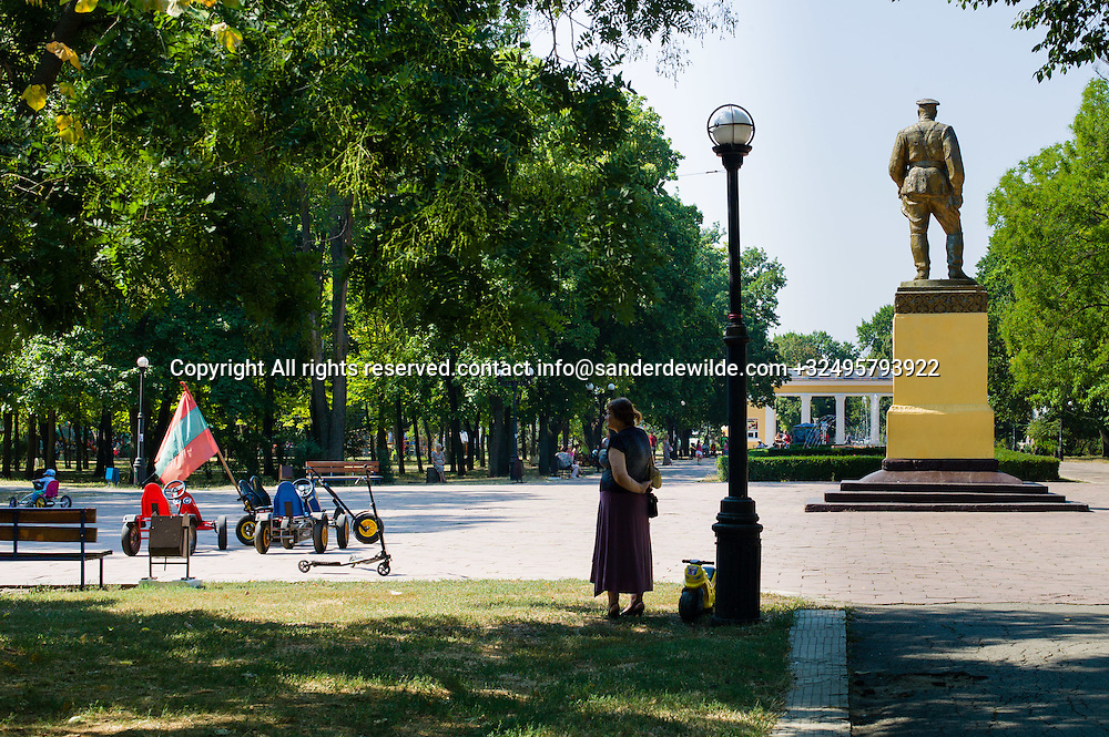 20150829  Moldova, Transnistria,Pridnestrovian Moldavian Republic (PMR) Tiraspol. A statue of a soldier ovelooking the Peboda park, and a mother watching her son while amusing himself with skelters, wearing the Transnistrian flag.