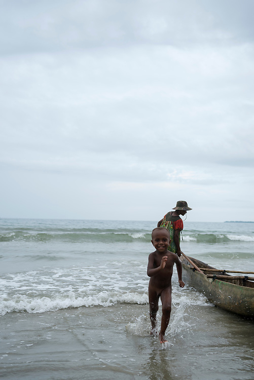 A young boy runs onto the beach after getting out of an outrigger canoe in Wewak, Papua New Guinea. His grandmother is beside the canoe. (July 2017)