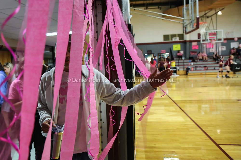 (10/15/19, MILLIS, MA) Spectators pass through a curtain of pink streamers as they walk into the gymnasium during the 13th annual Volleyball For A Cure night at Millis High School on Tuesday. [Daily News and Wicked Local Photo/Dan Holmes]