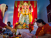 "23 SEPTEMBER 2018 - BANGKOK, THAILAND:  Prayers and blessings at the Ganesha Festival at Wat Dan in Bangkok. Ganesha Chaturthi also known as Vinayaka Chaturthi, is the Hindu festival celebrated on the day of the re-birth of Lord Ganesha, the son of Shiva and Parvati. The festival, also known as Ganeshotsav (""festival of Ganesha"") is observed in the Hindu calendar month of Bhaadrapada, starting on the the fourth day of the waxing moon. The festival lasts for 10 days, ending on the fourteenth day of the waxing moon. Outside India, it is celebrated widely in Nepal and by Hindus in the United States, Canada, Mauritius, Singapore, Thailand, Cambodia, and Burma.  PHOTO BY JACK KURTZ"