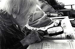 Elderly woman reading newspaper with magnifying glass in residential home for the elderly, Nottingham UK 1991