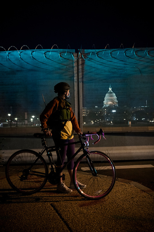 Washington DC, USA - January 21, 2021: Emily Gardner, 23, looks through the razor wire topped fence surrounding the U.S. Capitol Building. The fence was constructed after supporters of President Trump stormed the Capitol on January 6, 2021.