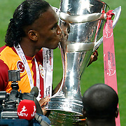 Galatasaray's Didier Drogba celebrate with the trophy after their Turkish Super League soccer match against Trabzonspor at Turk Telekom Arena stadium May 18, 2013.Galatasaray won the Turkish league title for the 19th time. Photo by Aykut AKICI/TURKPIX