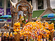 11 JULY 2011 - BANGKOK, THAILAND:  Flower garlands left as offerings rest on the Erawan Shrine in Bangkok. The Erawan Shrine (in Thai San Phra Phrom) is a Hindu shrine in Bangkok, Thailand that houses a statue of Phra Phrom, the Thai representation of the Hindu creation god Brahma. A popular tourist attraction, it often features performances by resident Thai dance troupes, who are hired by worshippers in return for seeing their prayers at the shrine answered. On 21 March 2006, a man vandalised the shrine and was subsequently killed by bystanders. The shrine is located by the Grand Hyatt Erawan Hotel, at the Ratchaprasong intersection of Ratchadamri Road in Pathum Wan district, Bangkok, Thailand. It is near the Bangkok Skytrain's Chitlom Station, which has an elevated walkway overlooking the shrine. The area has many shopping malls nearby, including Gaysorn, CentralWorld and Amarin Plaza. The Erawan Shrine was built in 1956 as part of the government-owned Erawan Hotel to eliminate the bad karma believed caused by laying the foundations on the wrong date..The hotel's construction was delayed by a series of mishaps, including cost overruns, injuries to laborers, and the loss of a shipload of Italian marble intended for the building. Furthermore, the Ratchaprasong Intersection had once been used to put criminals on public display. An astrologer advised building the shrine to counter the negative influences. The Brahma statue was designed and built by the Department of Fine Arts and enshrined on 9 November 1956. The hotel's construction thereafter proceeded without further incident. In 1987, the hotel was demolished and the site used for the Grand Hyatt Erawan Hotel.     PHOTO BY JACK KURTZ