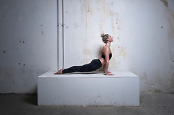 Mid adult woman practicing upward facing dog position on concrete block, Munich, Bavaria, Germany