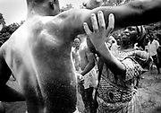 A woman helps young men cover themselves with talcum powder as they prepare for wrestling matches during the yearly evala festival in the town of Houde, northern Togo, on Thursday July 12, 2007. The powder, fighters say, makes it more difficult for their opponent to get a firm grasp.<br /> <br /> During the week-long tourney, young men wrestle against peers from their own and other villages. The evala festival is not only a sporting event, but also part of the rites of passage young men from the KabyŽ ethnic group will complete as they become full-grown men. The fighters, called evalo, will wrestle on three consecutive years to show their strength and their worth as they become full members of the community. <br /> <br /> Wrestlers cover themselves with talcum powder to allegedly make it more difficult for their opponent to get a firm grasp. Rubbing hands with dirt is also a popular technique which many believe helps counter the slippery effect of talcum powder. On the eve of the first day of fighting, the father of each evalo will buy a dog for his son to eat. It is believed that the meat of the animal will endow the young man with the strength and courage characteristic to the animal.<br /> <br /> While the wrestling is reserved to young men in their early to mid-twenties, younger boys also take part in unofficial matches as they prepare to become the next evalo. Even though supporters often become infuriated when their fighter is denied the victory they think he deserves, the outcome of the wrestling matches has little importance. Winners celebrate alongside those who are defeated and more than anything else, the evala festival is a social gathering where KabyŽs come to meet each other. Many KabyŽs in the diaspora even come home to attend the event. <br /> <br /> The first day of fighting pits evalos from two halves of a same village against each other. On the next day, fighters from an entire village wrestle against their peers from a neighbor settlement before 