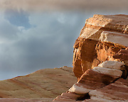 A sandstone rock formation in Valley of Fire State Park is spot lighted at sunset as storm clouds are present.
