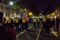 London, November 05 2017. Anti-capitalists gather in Trafalgar Square, London for the annual 'Million Mask March' which happens on November 5th every year, with many of the protesters donning 'V' For Vendetta Guy Fawkes masks. Past marches have turned violent with police horses shot by fireworks and police vehicles burned. PICTURED: Police follow protesters as they march back towards Trafalgar Square from Parliament Square. © Paul Davey