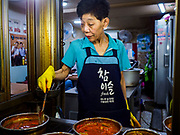 14 JUNE 2018 - SEOUL, SOUTH KOREA: A restaurant cook makes soups in Namdaemun Market. Namdaemun Market is one of the oldest continually running markets in South Korea, and one of the largest retail markets in Seoul. The streets in which the market is located were built in a time when cars were not prevalent, so the market itself is not accessible by car. The main methods of transporting goods into and out of the market are by motorcycle and hand-drawn carts. It occupies many city blocks, which are blocked off from most car traffic due to the prevalence of parking congestion in the area.       PHOTO BY JACK KURTZ