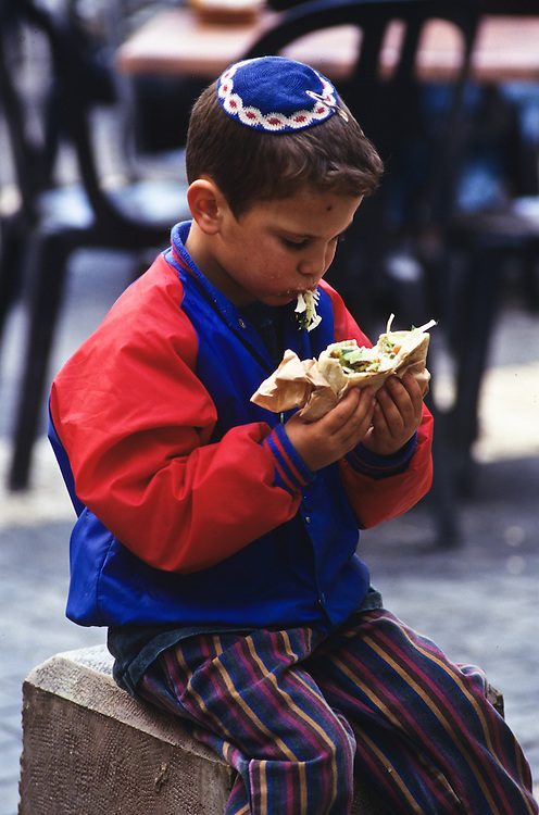 A young Jewish boy eating a sandwich on the street of Jerusalem.
