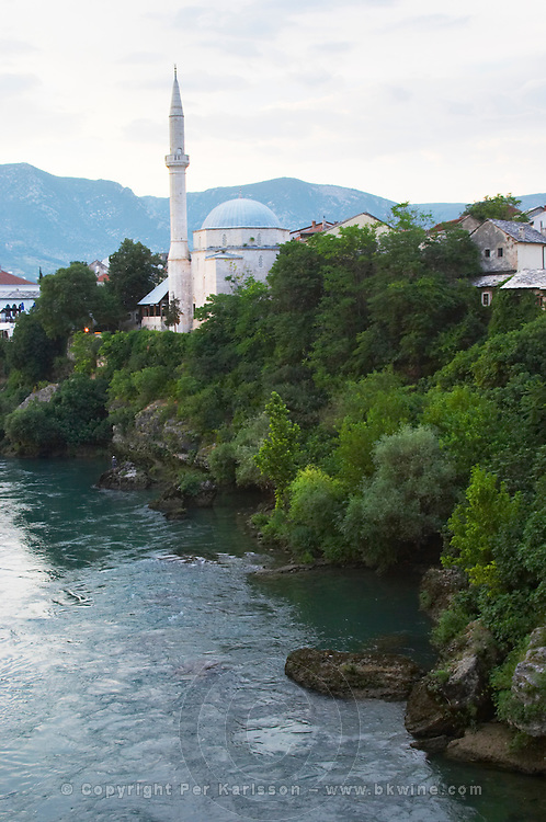 Koski Mehmed Pasha's Pasa mosque along the Neretva river seen from the old bridge. Historic town of Mostar. Federation Bosne i Hercegovine. Bosnia Herzegovina, Europe.
