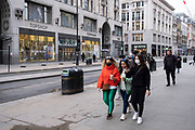 A few people on Oxford Street, some wearing face masks which is almost deserted in comparison to a normal day as the national coronavirus lockdown three continues on 4th March 2021 in London, United Kingdom. With the roadmap for coming out of the lockdown has been laid out, this nationwide lockdown continues to advise all citizens to follow the message to stay at home, protect the NHS and save lives.