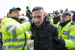 © Licensed to London News Pictures . 02/04/2016 . Dover , UK . An anti-fascist protester is handcuffed and lead away by police as anti-fascist protesters block the far-right march route . Demonstrations by far-right groups (including The National Front , The North West Infidels and The South East Alliance ) and , opposing them , anti-fascists , close to the port of Dover in Kent . Photo credit : Joel Goodman/LNP
