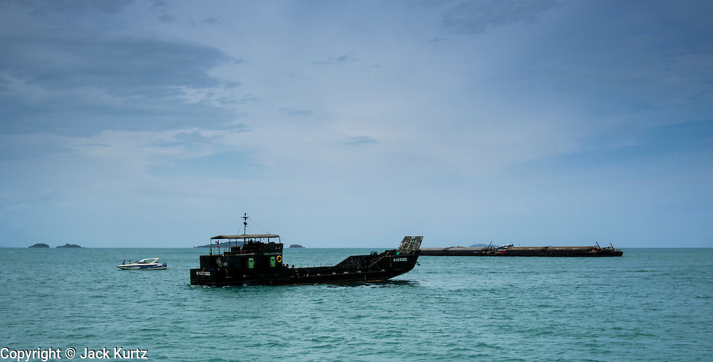 02 AUGUST 2013 - KOH SAMET, RAYONG, THAILAND:  A Royal Thai Navy landing craft approaches Koh Samet island to participate in the cleanup of an oil spill on the island. About 50,000 liters of crude oil poured out of a pipeline in the Gulf of Thailand over the weekend authorities said. The oil made landfall on the white sand beaches of Ao Prao, on Koh Samet, a popular tourists destination in Rayong province about 2.5 hours southeast of Bangkok. Workers from PTT Global, owner of the pipeline, and up to 500 Thai military personnel are cleaning up the beaches. Tourists staying near the spill, which fouled Ao Prao beach, were evacuated to hotels on the east side of the island, which was not impacted by the spill. PTT Global Chemical Pcl is part of state-controlled PTT Pcl, Thailand's biggest energy firm.   PHOTO BY JACK KURTZ