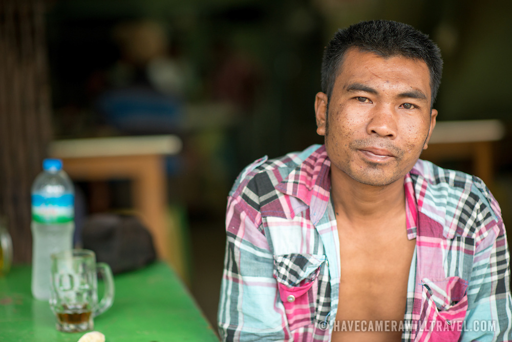 A local poses for a photo at the fish and flower market in Mandalay, Myanmar (Burma).