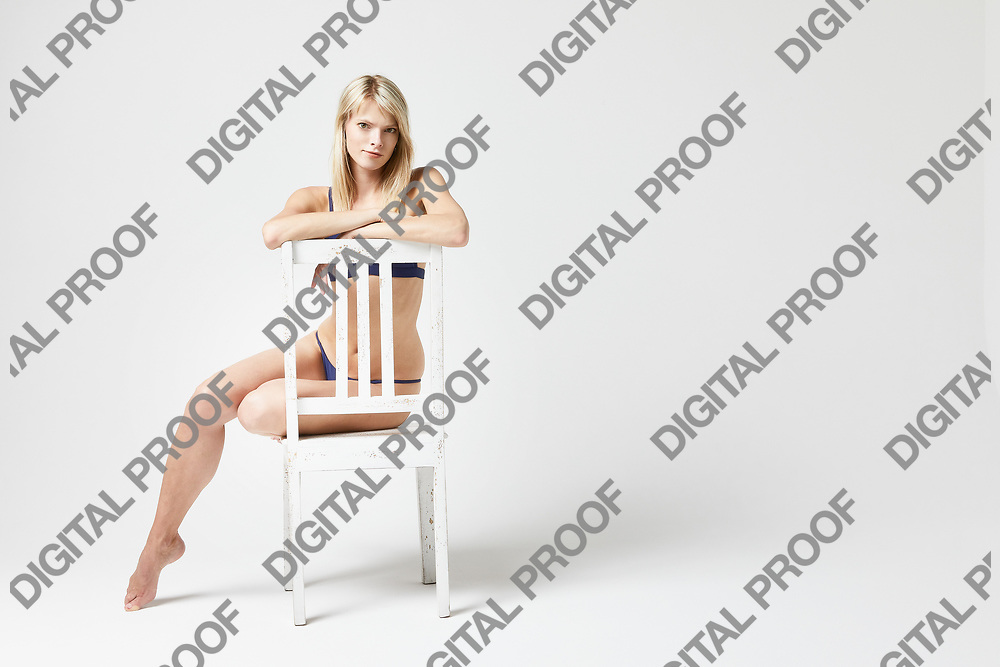 A woman with inquisitive mind seated and looking defiant while seated in a studio with a white background