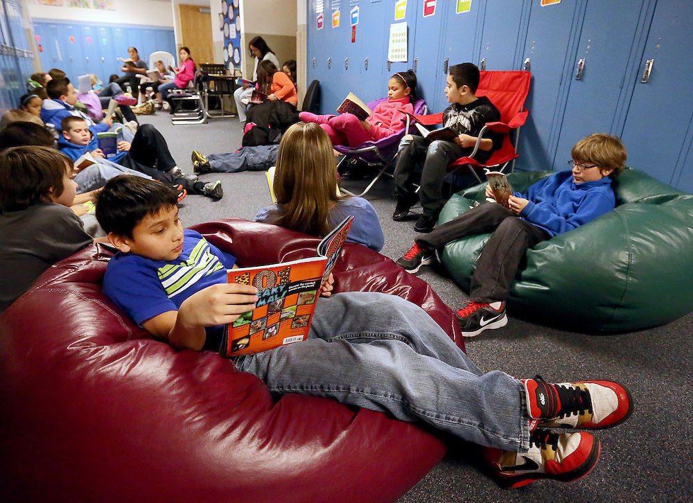 """Fourth-grader Javier Escalante reads """"101 Freaky Animals"""" by Melvin and Gilda Berger in the hallways at Dodge Elementary School Tuesday along with other classmates during a ?Read No Matter Where? event. The event is part of ?Read Across America Week? which was initiated by the National Education Association as a way to encourage reading and celebrate the birthday of famous children's author Dr. Seuss. (Independent/Matt Dixon)"""