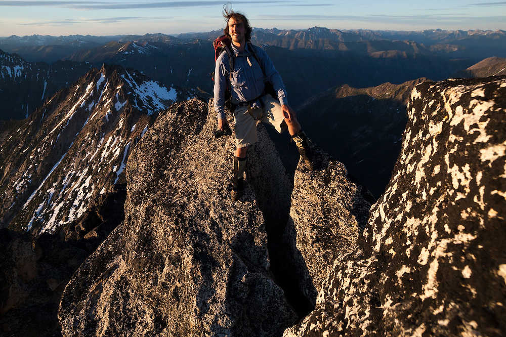 Kevin Steffa stands on the narrow summit block of Golden Horn at sunset in Okanogan National Forest, Washington.